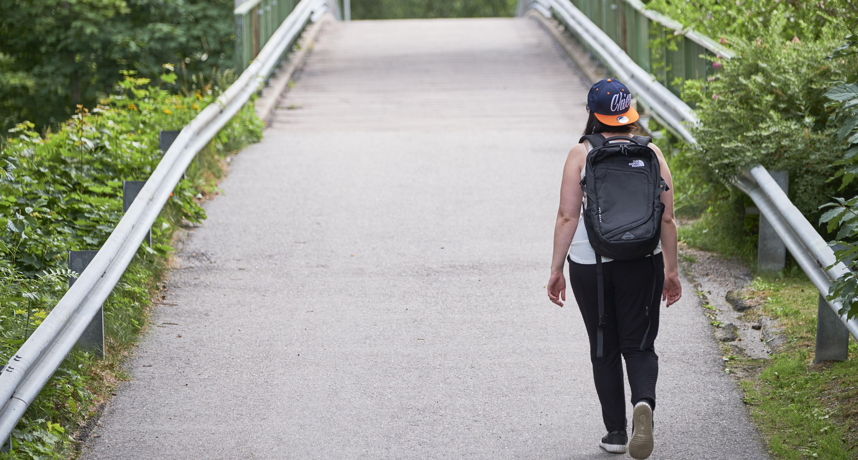 Opiskelija kävelee reppu selässään kohti siltaa.