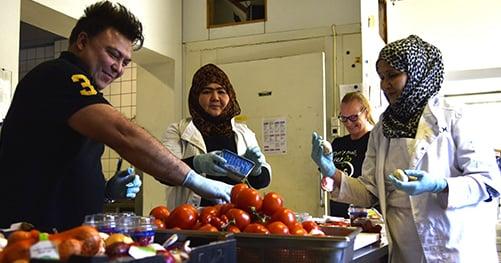 Neljä ihmistä keittiössä.