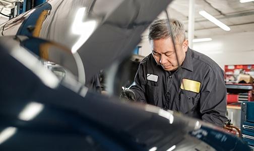 Mies työhaalareissa korjaa autoa.