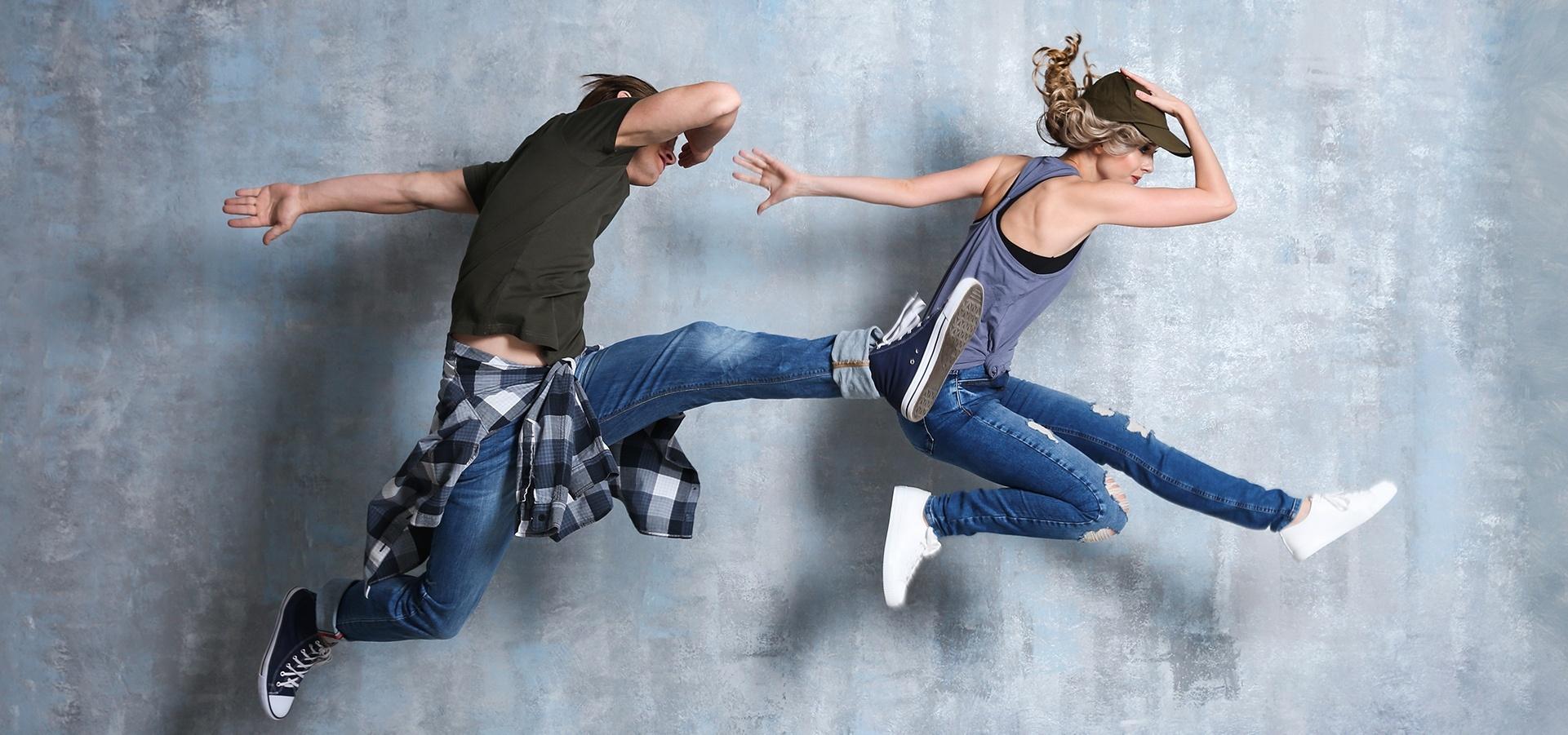 Kaksi tanssijaa hyppäävät ilmaan.