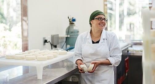 Nainen seisoo keittiössä, hymyilee ja pitää kädessään taikinaa.