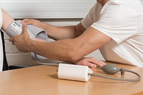 Hoitaja mittaa potilaalta verenpainetta.