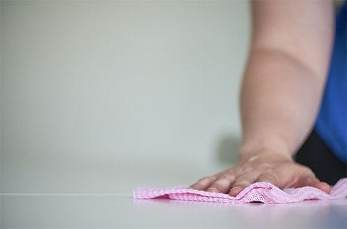 Rätillä pöytää pyyhkivä käsi.