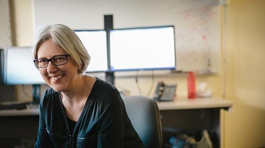 Nainen istuu tuolilla tietokone takanaan ja hymyilee.