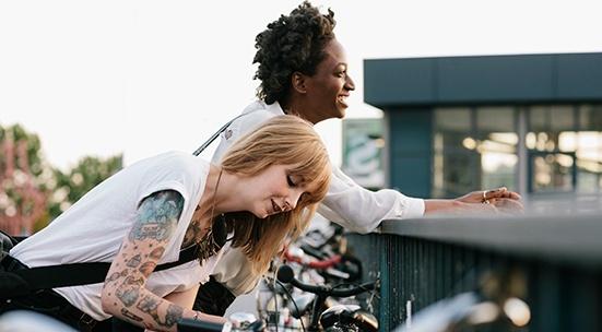 Kaksi naista seisovat vierekkäin. Toinen nojaa kaiteeseen ja hymyilee, toinen on kumartunut pyöränsä ylle.