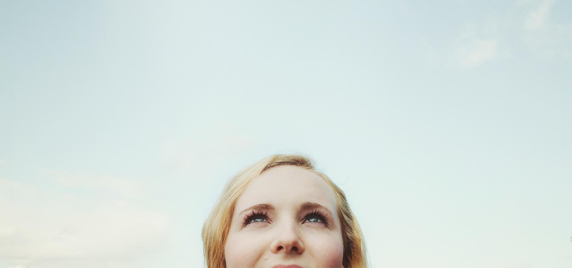 Nainen katsoo ylöspäin taivaalle kuvan alareunassa.