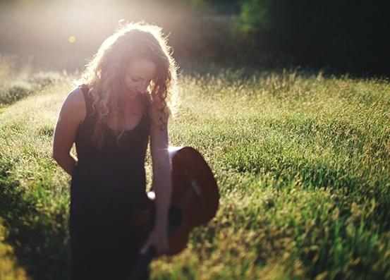 Nainen kävelee niityn laidalla auringonlaskussa kitara kädessä.