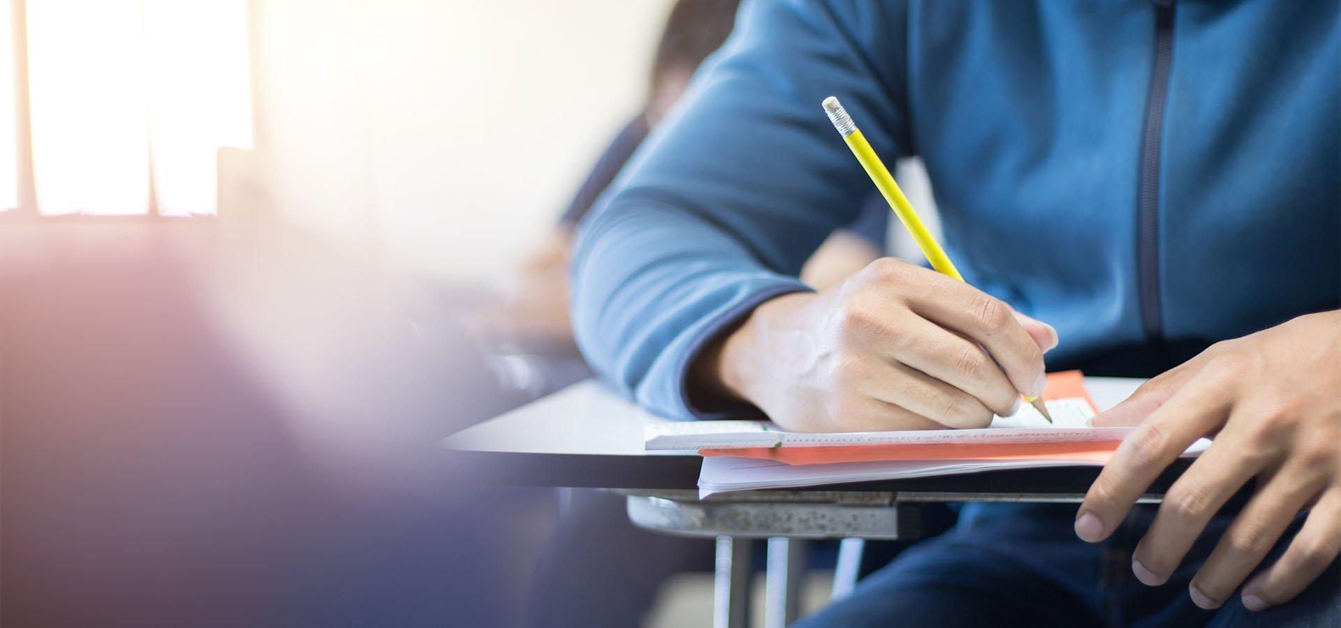 Sinipaitainen opiskelija istuu pulpetissa ja kirjoittaa lyijykynällä paperiin.