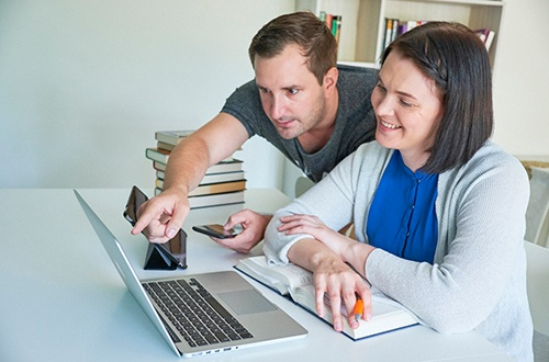 Nainen istuu pöydän ääressä, katsoo tietokonetta ja hymyilee. Vieressä seisoo mies ja neuvoo naiselle jotakin koneelta.