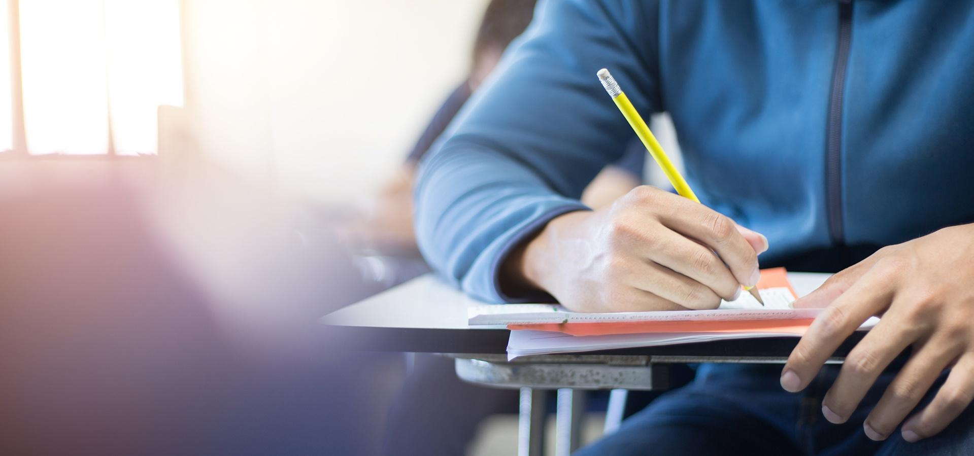 Kuvituskuva. Sinipaitainen opiskelija istuu pulpetissa ja kirjoittaa lyijykynällä paperiin.