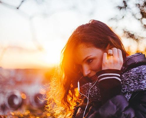 Nainen seisoo ilta-auringossa ja kuuntelee korvanapeista musiikkia.