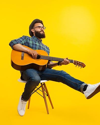 Kuvituskuva. Mies soittaa kitaraa.