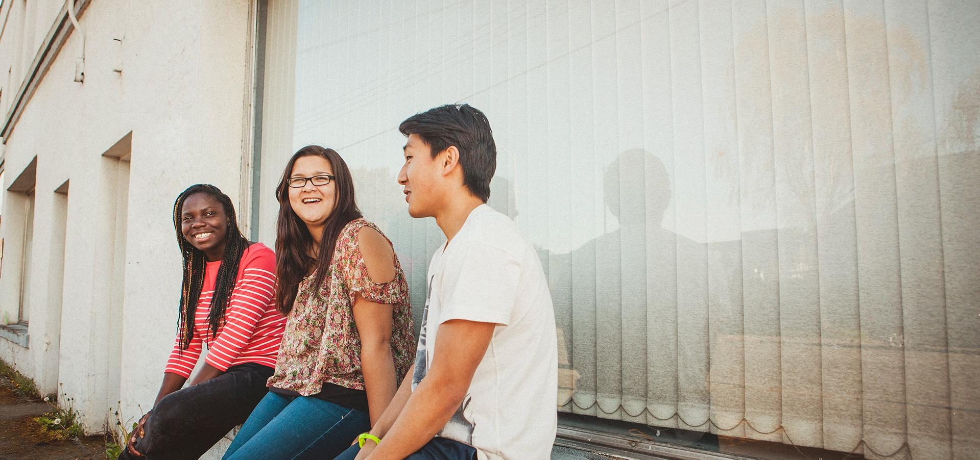Kolme opiskelijaa istuu ulkona ikkunan vieressä.