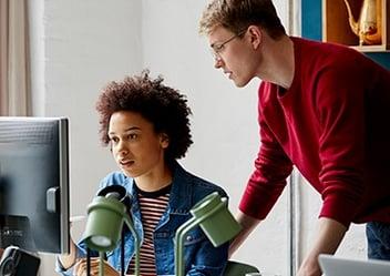 Nuori nainen istuu tietokoneen ääressä ja katsoo ruutua. Hänen viereensä on kumartunut punapaitainen mies neuvomaan häntä jossain.