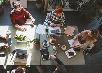 Ihmiset istuvat kokouspöydän ääressä tekemässä töitä, kuvattuna yläprofiilista.